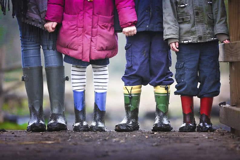 Kinder in Gummistiefeln auf Klassenfahrt